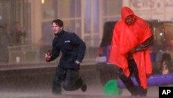 Gente busca cubrirse de una torrencial lluvia en el centro de Dallas, Texas.