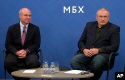 In this image made from video, Kremlin critic Mikhail Khodorkovsky, right, and financier William Browder attend a joint press conference in London, Nov. 20, 2018. They and other Kremlin foes have warned against naming a top Russian police official to lead Interpol.