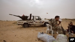 FILE - Libyan soldiers take a break from fighting with militants on the frontline in Al Ajaylat, 120 kilometers (75 miles) west of Tripoli, in this Feb. 21, 2015 photo.