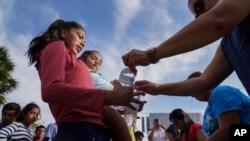 """Voluntarios entregan botellas de agua a decenas de migrantes, muchos de los cuales fueron devueltos a México bajo el programa """"Permanecer en México"""" del gobierno de Donald Trump, en un campamento en Matamoros, México."""