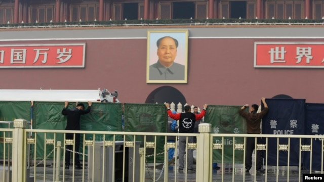 Police officers set up barriers in front of the giant portrait of the late Chinese Chairman Mao Zedong as they clean up after a car accident at Tiananmen Square in Beijing, Oct. 28, 2013.