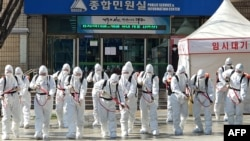 South Korean soldiers wearing protective gear spray disinfectant as part of preventive measures against the spread of the COVID-19 coronavirus, at city hall in Daegu on March 2, 2020. - South Korea confirmed 599 new coronavirus cases on March 2, taking th