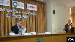 Ashvin Dayal, Associate VP and Asia Managing Director, The Rockefeller Foundation (left) looks over his notes as USAID Asia Regional Development Mission Director Michael Yates at launch of Global Resilience Partnership, Aug. 19, 2014. (Steve Herman/VOA News)