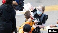 Žena poliva mlekom lice demonstranta koga je policija isprskala suzavcem drugog dana protesta u Mineapolisu.