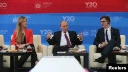 Russia's President Vladimir Putin, center, meets with representatives of G20 Youth Summit, St.Petersburg International Economic Forum, June 20, 2013.