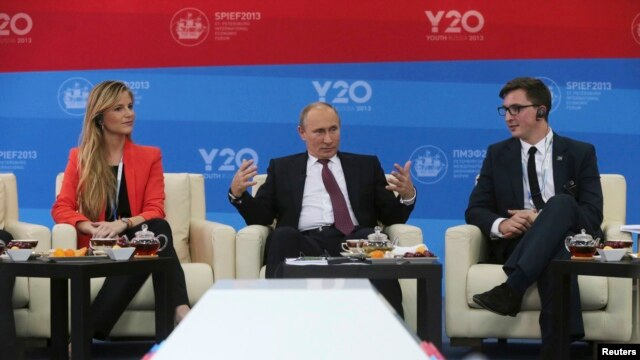 Russia's President Vladimir Putin, center, meets with representatives of G20 Youth Summit, St.Petersburg International Economic Forum, June 20, 2013.