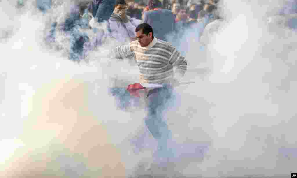 A protester carrying an Egyptian flag runs through clouds of tear gas at a demonstration in Cairo, Jan. 25, 2011.