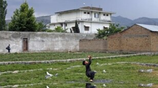 FILE - A boy plays with a tennis ball in front of Osama bin Laden's compound in Abbottabad, Pakistan, May 2011.