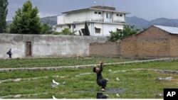 FILE - A boy plays with a tennis ball in front of Osama bin Laden's compound in Abbottabad, Pakistan, May 2011. Osama bin Laden was killed at his compound on May 2, 2011, by a U.S. special forces team.