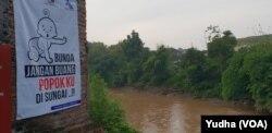 Warga diingatkan untuk tidak membuang popok bayi di sungai dengan Pesan Layanan Masyarakat yang dipasang di salah satu sisi sungai di Solo, Jumat (22/3). (Foto: VOA/Yudha)