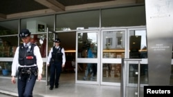 Polisi meninggalkan gedung Asosiasi Sosial Budaya Polandia, tempat adanya grafiti yang menyerukan orang-orang Polandia untuk pulang ke negaranya, di Hammersmith, London (27/6). (Reuters/Neil Hall)