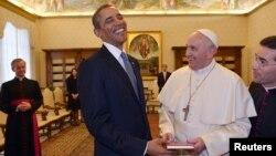 Paus Fransiskus (kanan) memberi Presiden Obama sebuah dokumen kepausan berjudul 'The Joy of Gospel' di Vatikan, Kamis (27/3).