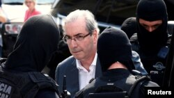 Former speaker of Brazil's Lower House of Congress, Eduardo Cunha (C), is escorted by federal police officers as he leaves the Institute of Forensic Science in Curitiba, Oct. 20, 2016.