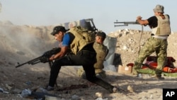 Iraqi security forces defend their positions against an Islamic State group attack in Husaybah, Iraq, June 15, 2015.