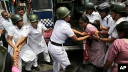 Indian policewomen detain an activist of Socialist Unity Center of India during a daylong nationwide strike in Kolkata, India, Sept. 2, 2015.