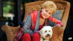 """Debbie Reynolds, yang ikut berperan dalam film """"Behind the Candelabra,"""" berpose bersama anjingnya, Dwight, di Beverly Hills, California, 21 Mei 2013. Reynolds meninggal dunia di usia 84 tahun, Rabu siang (28/12) sehari setelah putrinya, Carrie Fisher tutup usia."""
