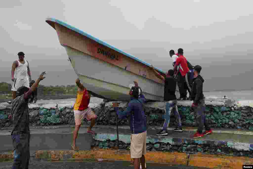 Men take a boat off a beach before the arrival of Tropical Storm Fred in Santo Domingo, Dominican Republic, Aug. 11, 2021.