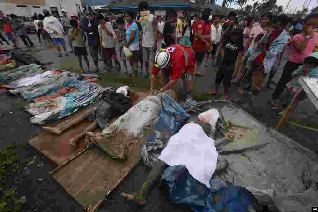 Một nhân viên cứu hộ lấy vải phủ lên xác các nạn nhân chết do lũ quét trong tỉnh Compostela Valley miền nam.