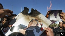 Protesters burn a photo of former Tunisian President Zine El Abidine Ben Ali during a demonstration in Tunis, 24 Jan 2011