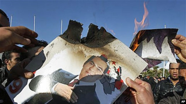 Protesters burn a photo of former Tunisian President Zine el-Abidine Ben Ali during a demonstration in Tunis, 24 Jan 2011