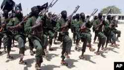FILE - Hundreds of newly trained al-Shabab fighters perform military exercises in the Lafofe area, south of Mogadishu, Somalia.