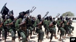 FILE - Hundreds of newly trained al-Shabab fighters perform military exercises near Mogadishu, Somalia.