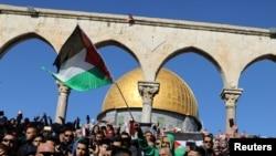 Fieles ondean la bandera palestina durante protestas tras las oraciones del viernes en el complejo conocido para los musulmanes como el Noble Santuario y para los judíos como Templo del Monte en la ciudad vieja de Jerusalén, el viernes, 8 de diciembre de 2017.