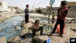 FILE - An Iraqi boy is seen drinking water from a broken pipe in Baghdad's Sadr City, Iraq.