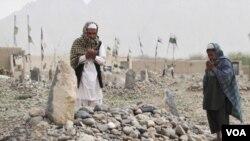 Dua orang warga Afghanistan mengunjungi makam keluarga mereka yang tewas dalam pembunuhan di Distrik Panjawi.
