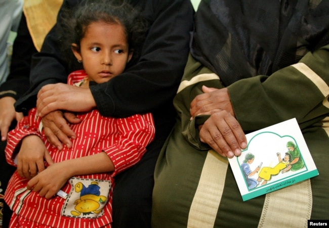 A woman holds a card in her lap about the problems with female genital mutilation (FGM) during a session to educate women in Minia, Egypt June 13, 2006.