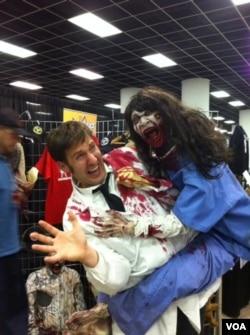 Seorang pria memegang boneka zombie di konvensi Walker Stalker di Atlanta, Georgia. (VOA/Marissa Melton)