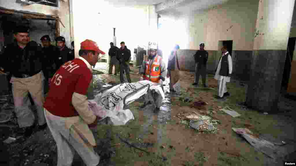 Rescue workers carry the covered body parts of a suspected suicide bomber at the site of bomb blast in a judicial compound in Peshawar, March 18, 2013.