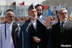 Afghan President Hamid Karzai, center, calls for resolution in presidential election. He's flanked by candidates Ashraf Ghani, left, and Abdullah Abdullah in Kabul Aug. 19, 2014.