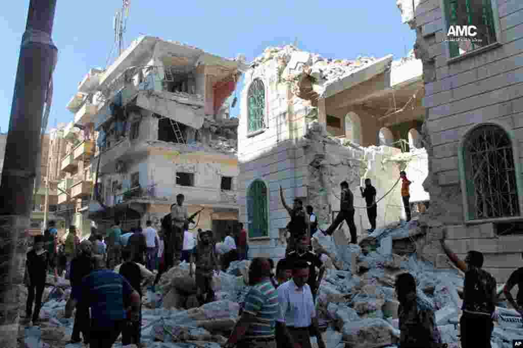 In this June 29, 2013 citizen journalism image, Syrian rebels inspect the rubble of damaged buildings due to a surface-to-surface missile launched by Syrian forces in Aleppo, Syria.