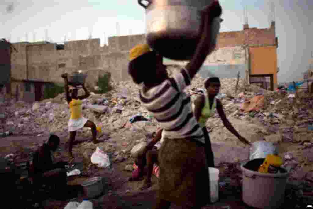 19 Ocak: Haiti'nin başkenti Port-au-Prince'de akşam saatinde boşalan yemek kazanlarını taşıyan seyyar satıcılar. (AP/Rodrigo Abd)