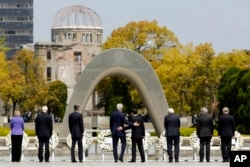 U.S. Secretary of State John Kerry, center left, puts his arm around Japan's Foreign Minister Fumio Kishida, center right, after they and fellow G7 foreign ministers laid wreaths at the cenotaph at Hiroshima Peace Memorial Park in Hiroshima, western Japan