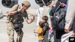 کابل ایئر پورٹ پر ایک امریکی فوجی انخلا کے منتظر دو بچوں سے گفتگو کر رہا ہے۔ 24 اگست 2021