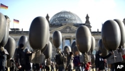 Demonstrators hold balloons in front of the Reichtags building to protest against arms trade, Germany, February 26, 2012.