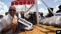 Ross Dunkley, the editor-in-chief of the English-language Myanmar Times, poses for a photo with packs of heroin during a ceremony to destroy seized narcotic drugs in Lashio, northeast of Rangoon, Burma (FILE)