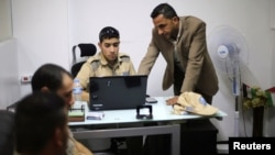 Palestinian Akram Al-Balawi (R), director of Castle Security company, speaks with a private security guard in the company's office in Gaza City, Nov. 21, 2016.