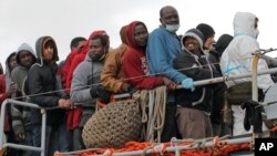 Migrants wait to disembark from a tug boat after being rescued in Porto Empedocle, Sicily, southern Italy, Feb. 17, 2015.