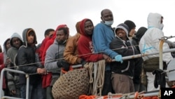 FILE - Migrants wait to disembark from a tug boat after being rescued in Porto Empedocle, Sicily, southern Italy, Feb. 17, 2015.
