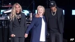 ທ້າວ Jay Z (ຂວາ) ແລະນາ Beyonce (ຊາຍ) ຢູ່ຄຽງຂ້າງ ຜູ້ສະມັກປະທານາທິບໍດີພັກເດໂມແຄຣັດ ທ່ານນາງ Hillary Clinton ໃນລະຫວ່າງ ການໂຄສະນາຫາສຽງ ທີ່ນະຄອນ Cleveland ລັດ Ohio ໃນວັນທີ 4 ພະຈິກ.