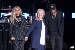 FILE: Jay-Z, right, and Beyonce, left, stand with Democratic presidential candidate Hillary Clinton during a campaign rally in Cleveland, Nov. 4, 2016.