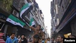 Bustan el/Kasr kentinde muhalefet bayrakları sallayan Esad karşıtı göstericiler