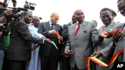 Senegalese President Abdoulaye Wade cuts the ribbon at the ceremony next to his son, State Minister for Air Transport Karim Wade