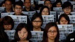 Nhân viên của tờ Minh Báo cùng cầm tờ báo có trang nhất đăng bài viết về vụ tấn công ông Lưu Tiến Đồ, cựu chủ biên tờ báo này