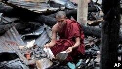 Seorang biksu Buddha Bangladesh memeriksa sisa-sisa buku agama yang terbakar habis bersama kuil Buddha dalam serangan hari Sabtu dan Minggu di Ramu, wilayah Cox's Bazar, Bangladesh (1/10).