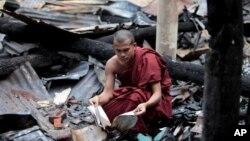1일 방글라데시 콕스 바자르 지역의 사원에서 회교도들의 공격으로 인해 불에 탄 법전을 수습하는 승려.