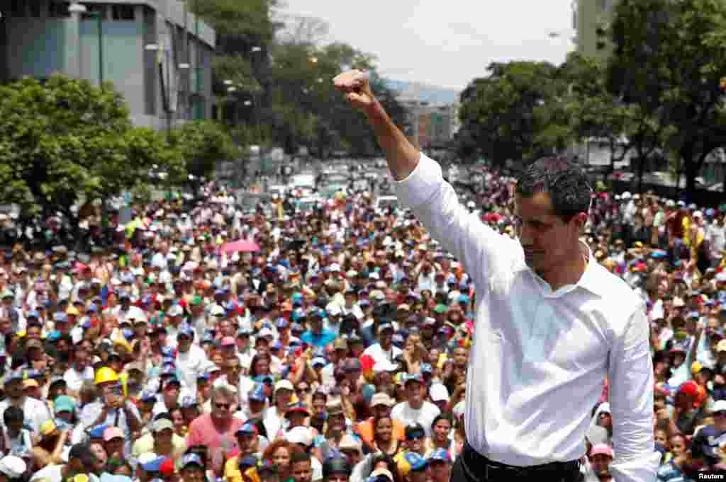 Venezuelan opposition leader Juan Guaido, whom many nations have recognized as the country's rightful interim ruler, gestures as he speaks to supporters during a rally against the government of President Nicolas Maduro and to commemorate May Day in Caraca